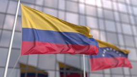 Waving flags of Colombia and Venezuela in front of a modern skyscraper facade