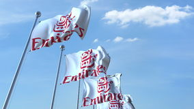 Waving flags with Emirates Airlines logo against sky, editorial 3D rendering Royalty Free Stock Photography