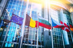 Waving flags in front of European Parliament building, Brussels royalty free stock image