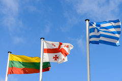 Waving flags of Lithuania, Georgia and Greece against the blue s Royalty Free Stock Photos