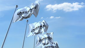 Waving flags with Nissan logo against sky, editorial 3D rendering. Waving flags with Nissan logo against sky, editorial 3D Stock Photo
