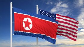 Waving flags of North Korea and USA on flagpole Stock Photo