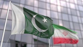 Waving flags of Pakistan and Iran in front of a modern skyscraper facade