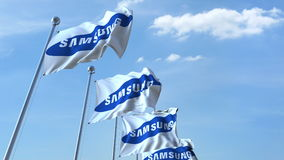 Waving flags with Samsung logo against sky, editorial 3D rendering Stock Photos