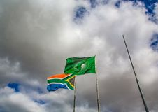 Waving flags of South Africa and the African Union. In front of cloudy sky stock photography