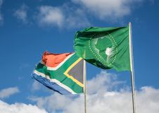Waving flags of South Africa and the African Union. In front of cloudy sky royalty free stock photography