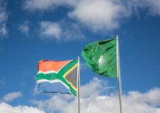 Waving flags of South Africa and the African Union. In front of cloudy sky stock images