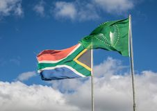 Waving flags of South Africa and the African Union. In front of cloudy sky stock photo