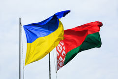 Waving flags of Ukraine and Belarus. Symbol of friendship and partnership. Waving flags of Ukraine and Belarus on flagpoles against the sky Stock Image