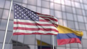 Waving flags of the United States and Colombia in front of a modern skyscraper facade