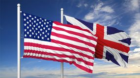 Waving flags of USA and UK on flagpole Royalty Free Stock Image