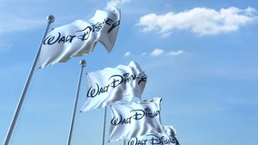 Waving flags with Walt Disney logo against sky, editorial 3D rendering. Waving flags with Walt Disney logo against sky, editorial 3D Stock Photos