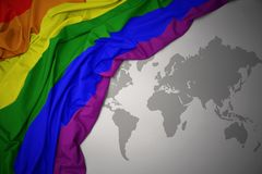 Waving gay rainbow flag. Waving colorful gay rainbow flag of on a gray world map background stock image