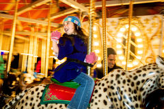 Waving Girl On Carousel Riding Jaguar. A young girl rides a carousel in winter. She has on a hat, warm coat, and gloves. She is waving at someone she just passed Stock Image