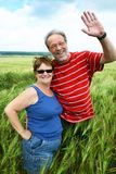Waving goodbye. A cute senior couple standing in a field waving goodbye royalty free stock photo