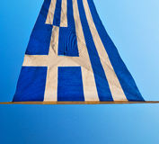 waving greece flag in    the blue sky and flagpole Stock Images