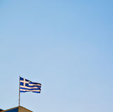 Waving greece flag in the blue sky and flagpole Stock Image