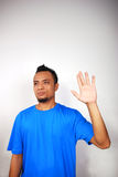 Waving Hand. Young man with blue shirt raising hand in 'high five' or tentative wave, isolated background royalty free stock photography