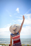 Waving hand elegant lady in straw hat looking into Royalty Free Stock Photo