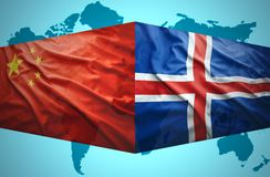 Waving Icelandic and Chinese flags. Of the political map of the world Royalty Free Stock Images