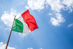 Waving Italian flag against blue sky. Royalty Free Stock Photography
