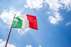 Waving Italian flag against blue sky. Stock Photo