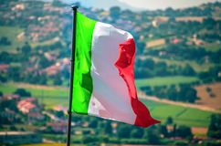 Waving italian flag wave countryside background royalty free stock photography
