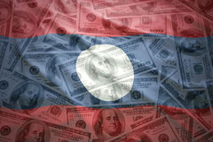 Waving laotian flag on a american dollar money background Royalty Free Stock Images
