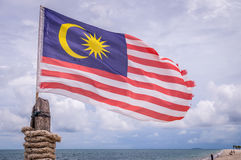 Waving Malaysian flag on beach in Langkawi. Malaysian flag attached on pole waving on beach in Langkawi island on a cloudy day royalty free stock images