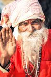 Waving man in West Bengal. Ganga Sagar, West Bengal - circa January 2012: Old native man in red clothes with grey beard wears headcloth and waves to photocamera Royalty Free Stock Image