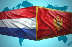 Waving Montenegrin and Dutch flags. Of the political map of the world Stock Photography