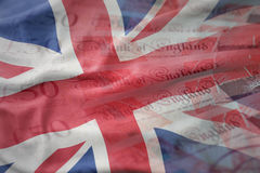 waving national flag of great britain on a pounds money banknotes background. finance concept Royalty Free Stock Photo