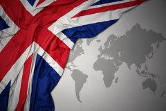 Waving national flag of great britain. Waving colorful national flag of great britain on a gray world map background Royalty Free Stock Photo