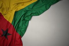 Waving national flag of guinea bissau on a gray background. Waving colorful national flag of guinea bissau on a gray background royalty free stock images
