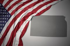 Waving national flag of united states of america on a gray kansas state map background. Waving colorful national flag of united states of america on a gray royalty free stock photos