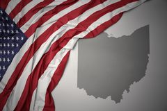 Waving national flag of united states of america on a gray ohio state map background. Waving colorful national flag of united states of america on a gray ohio stock photography