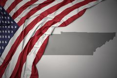 Waving national flag of united states of america on a gray tennessee state map background. Waving colorful national flag of united states of america on a gray royalty free stock photo