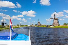 Waving Netherlands flag on a cruise ship against famous windmills in Kinderdijk village in Holland. Colorful spring rural landscap. E in Netherlands, Europe stock images