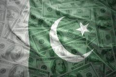 Waving pakistani flag on a american dollar money background. Colorful waving pakistani flag on a american dollar money background Royalty Free Stock Photo