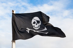 Waving Pirate flag. Isolated on blue sky Royalty Free Stock Image