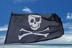 Waving pirate flag jolly roger on tropical island background. Waving pirate flag jolly roger on sky background royalty free stock images