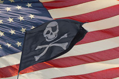 Waving pirate flag jolly roger on usa star and stripes Royalty Free Stock Image
