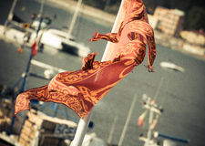 Waving in the port. Boat flag flying in the harbor Stock Photos