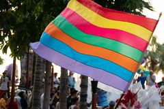 Waving rainbow of gay flag and crowd of people in Pride Rainbow Festival Parade. LGBT rights concept stock photos
