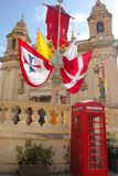 Waving red, yellow and white flags on festively decorated square near old beautiful church and red telephone both for annual festa stock photo