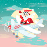 Waving Santa Claus flying on the plane with sack full of presetn Royalty Free Stock Images