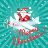 Waving Santa Claus flying on the plane with sack full of presetn Stock Photos