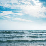 Waving sea and cloudy sky with sun Royalty Free Stock Image