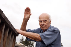Waving Senior Neighbor Outdoors. Senior man waves hello, to his neighbors outside, with one hand on the deck, ready to go inside Stock Images