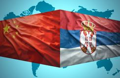 Waving Serbian and Chinese flags. Of the political map of the world Stock Photo